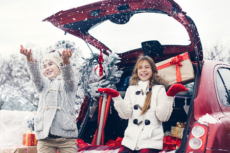 Photo pour Holiday preparations. Pre teen children enjoy many Christmas presents in car trunk. Cold winter, snow weather. - image libre de droit