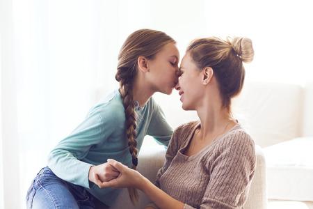 Foto de Pre teen daughter kissing her mom, positive feelings, good relations. - Imagen libre de derechos