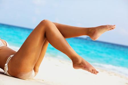 Photo pour Women's beautiful sexy legs on the beach - image libre de droit