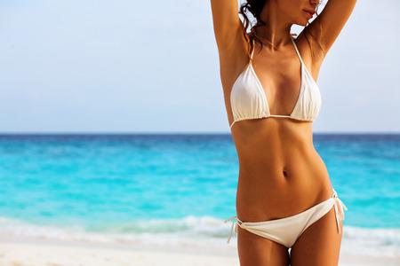 Foto de Beautiful woman's body in sexy bikini over beach background - Imagen libre de derechos