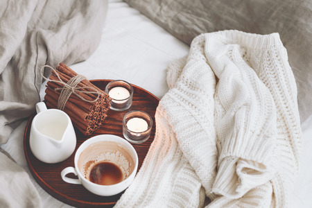 Photo pour Wooden tray with coffee, milk, cinnamon sticks and tea candles in the bed, lasy morning, warm winter mood - image libre de droit