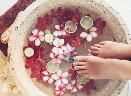 Foto de Foot bath in bowl with lime and tropical flowers, spa pedicure treatment, top view - Imagen libre de derechos