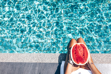 Photo pour Girl holding watermelon in the blue pool, slim legs. - image libre de droit