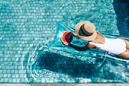Photo pour Girl floating on beach mattress and eating watermelon in the blue pool. Tropical fruit diet. Summer holiday idyllic. Top view. - image libre de droit