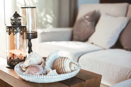 Photo pour Beach interior decor: sea shells and lanterns on the wooden coffee table, natural colors. Detail of living room. - image libre de droit