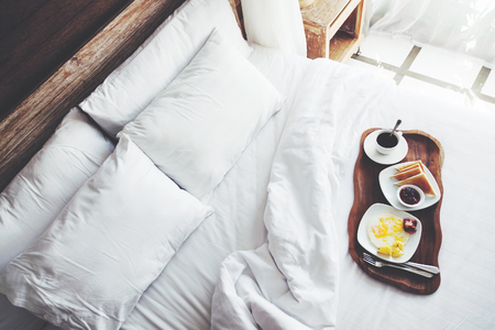 Photo pour Brekfast on a tray in bed in hotel, white linen, wooden intreior - image libre de droit