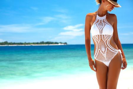 Foto de Beautiful woman wearing crochet bikini posing over the sea view, beach lifestyle - Imagen libre de derechos
