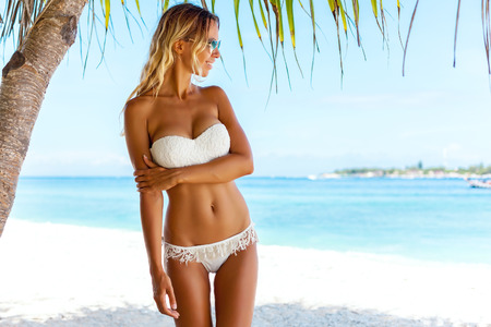 Foto de Young woman wearing white bikini posing under palm tree over sea view at tropical beach - Imagen libre de derechos