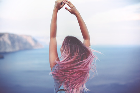 Photo pour Woman with pink hair standing on the mountain top over blue sea view, photo toned - image libre de droit