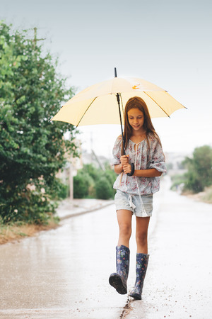 Photo pour Preteen child wearing rubber boots and holding umbrella walking in the rain - image libre de droit