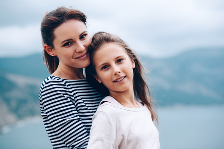 Photo for Mom and her teenage daughter hugging and smiling together over blue sea view - Royalty Free Image
