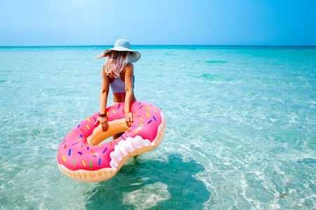 Photo for Woman swimming with inflatable donut on the beach in summer sunny day - Royalty Free Image