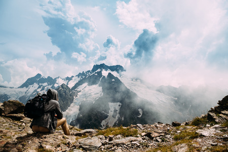 Photo pour Lonely man with backpack sitting on the top of the mountain and looking at beautiful landscape - image libre de droit