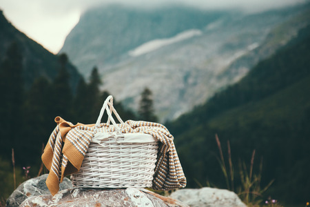 Photo pour Closeup photo of wicker basket with blanket over mountains view, picnic in cold season - image libre de droit