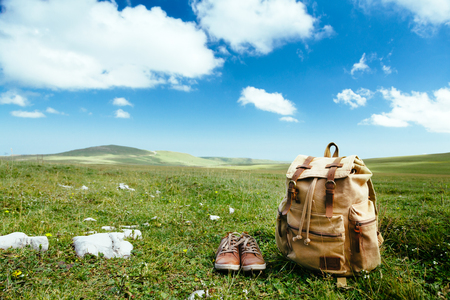 Photo pour Travel backpack and shoes on green grass in spring field, blue sky and clouds, idyllic scene - image libre de droit