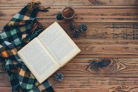 Photo pour Mug with tea bag, book and plaid winter blanket on vintage wooden table, top view - image libre de droit