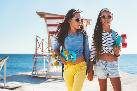 Photo for Two 10 years old children wearing cool clothing posing with colorful skateboards on the beach in sunlight, urban style, pre teen summer fashion. - Royalty Free Image