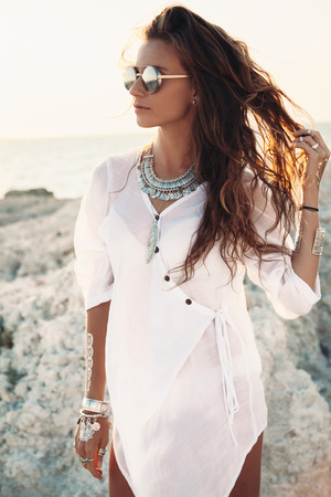Photo for Beautiful boho styled girl wearing white shirt with fashion ethnic jewelery and flash tattoo at the beach in sunlight - Royalty Free Image