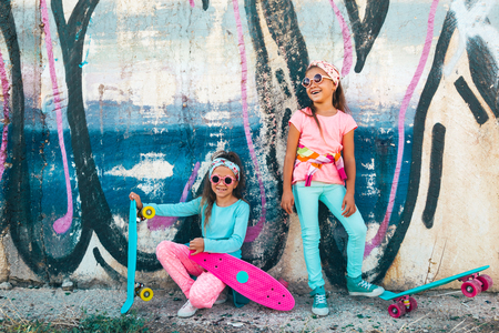 Photo for Two 7 years old children wearing cool fashion clothing posing with colorful skateboard against graffiti wall, urban style - Royalty Free Image