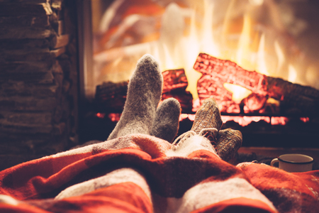 Photo pour Cold fall or winter evening. People resting by the fire with blanket and tea. Closeup photo of feet in woolen socks. Cozy scene. - image libre de droit