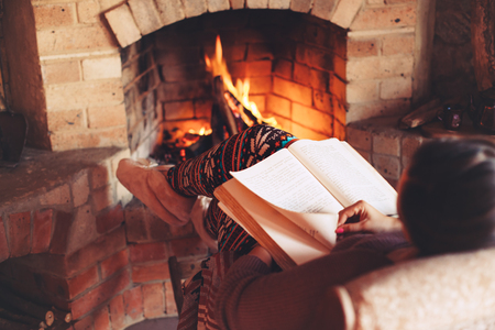 Photo for Woman reading book and relaxing by the fire place some cold evening, winter weekends, cozy scene - Royalty Free Image