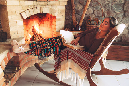 Photo pour Woman reading book and relaxing by the fire place some cold evening, winter weekends, cozy scene - image libre de droit
