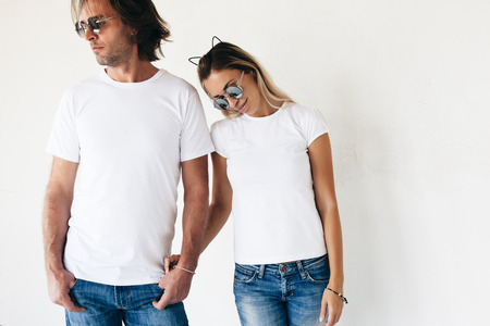 Photo pour Two hipster models man and woman wearing blanc t-shirt, jeans and sunglasses posing against white wall, toned photo, front tshirt mockup for couple - image libre de droit