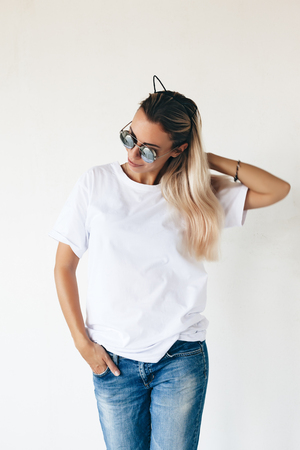 Photo pour Woman wearing blanc t-shirt posing against white wall, toned photo, front tshirt mockup on model, hipster style - image libre de droit