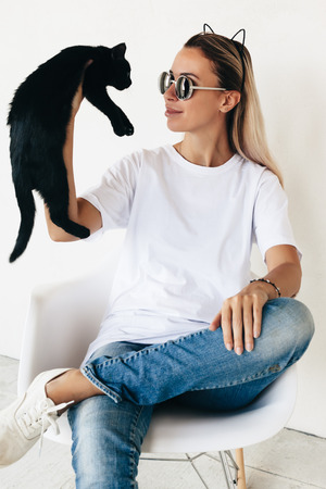 Foto de Woman wearing blanc t-shirt, jeans and sneakers sitting on chair and playing with black kitten, toned photo, front tshirt mockup on model, hipster style - Imagen libre de derechos