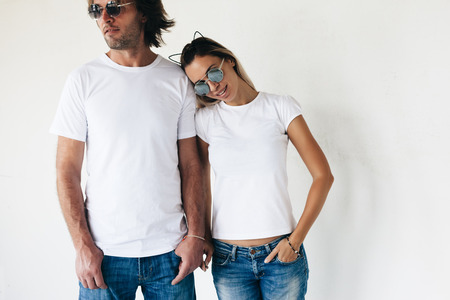Foto de Two hipster models man and woman wearing blanc t-shirt, jeans and sunglasses posing against white wall, toned photo, front tshirt mockup for couple - Imagen libre de derechos