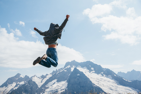 Photo pour Unrecognizable man jumping on top of the mountain over blue skies, freedom and joy - image libre de droit