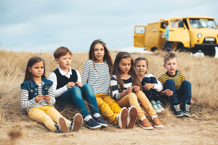 Photo for Group of fashion children wearing same style clothing having fun in the autumn field. Fall casual outfit in navy and yellow colors. 7-8, 8-9, 9-10 years old models. - Royalty Free Image