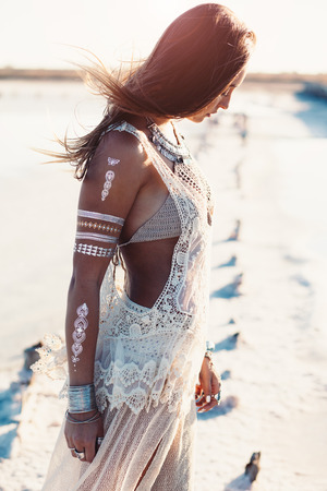 Foto de Beautiful girl wearing bohemian chic clothing with flash tattoo on her body posing on the shore in sunlight - Imagen libre de derechos