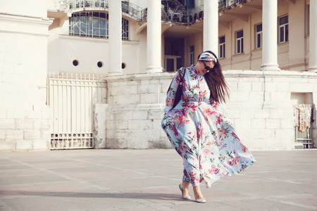 Photo pour Plus size model wearing floral maxi dress posing on the city street. Young and fashionable overweight woman walking around town. - image libre de droit