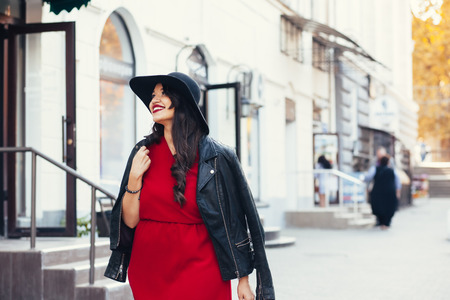Photo for Young stylish woman wearing red maxi dress, black leather jacket and hat walking on the city street in autumn. Fall fashion, elegant look. Plus size model. - Royalty Free Image