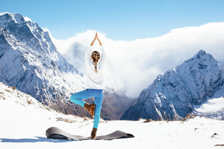 Foto de Young woman practicing yoga pose outdoors in winter. Streching workout in snow on top of mountain. Hiking in cold season. Calm and silent view. - Imagen libre de derechos