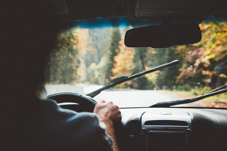 Photo pour Man driving car in rain weather. Fall trip. Wipers cleaning windshield. Freedom travel concept. Autumn weekend. - image libre de droit