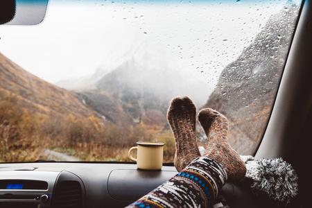 Foto de Woman legs in warm socks on car dashboard. Drinking warm tee on the way. Fall trip. Rain drops on windshield. Freedom travel concept. Autumn weekend in mountains. - Imagen libre de derechos