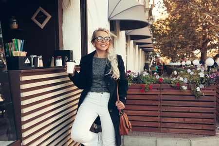 Photo for Blond woman wearing black midi coat, white pants, hipster glasses drinking take away coffee in paper cup in outdoor cafe on city street. Fall casual fashion, elegant everyday look. Plus size model. - Royalty Free Image