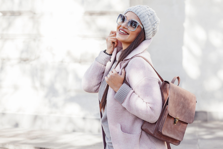 Photo pour Young stylish woman wearing pink warm coat, pants and handbag walking in the city street in cold season. Winter fashion, elegant look, outfit in pastel colors. Plus size model. - image libre de droit
