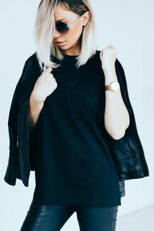 Foto de Fashion model in black clothing. Leather jacket and pants, blank t-shirt and sunglasses. Street urban style. - Imagen libre de derechos