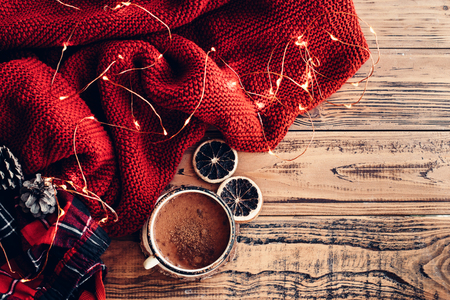 Photo pour Winter homely scene. Warm knit blanket and cup of hot cocoa, led lights string. Christmas holiday decor. - image libre de droit