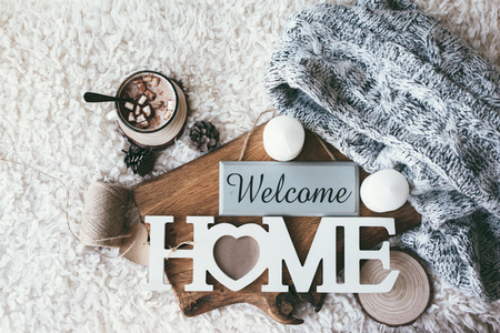 Foto per Winter homely scene, scandinavian style. Warm knit sweater, candles, cup of sweet cocoa with marshmallows and other decor on tray in bed. Wooden craft letters Welcome Home. Lazy cold weekend. - Immagine Royalty Free
