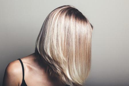 Photo pour Model with unrecognizable face with blond shiny hair. Woman bob haircut styling. - image libre de droit