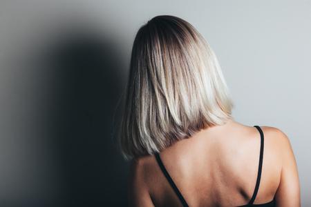 Foto de Model with unrecognizable face with blond shiny hair. Woman bob haircut styling. Back view - Imagen libre de derechos