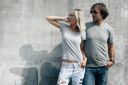 Photo pour Two hipster models man and woman wearing blank gray t-shirt, jeans and sunglasses posing against rough concrete wall in the city street, front tshirt mockup for couple, urban style - image libre de droit