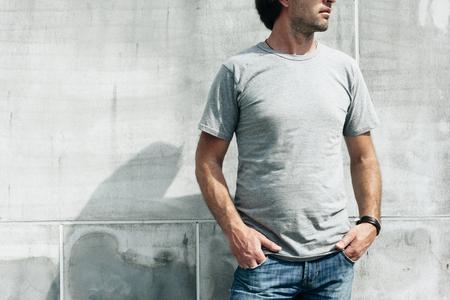 Foto de Man wearing blank t-shirt posing against gray concrete wall in the city street, front tshirt mockup on model, urban style - Imagen libre de derechos