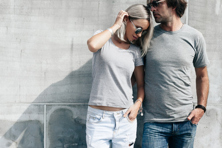 Foto de Two hipster models man and woman wearing blank gray t-shirt, jeans and sunglasses posing against rough concrete wall in the city street, front tshirt mockup for couple, urban style - Imagen libre de derechos
