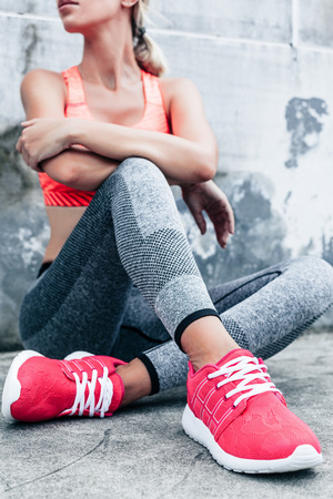Photo for Fitness sport woman in fashion sportswear doing yoga fitness exercise in the city street over gray concrete background. Outdoor sports clothing and shoes, urban style. Sneakers closeup. - Royalty Free Image