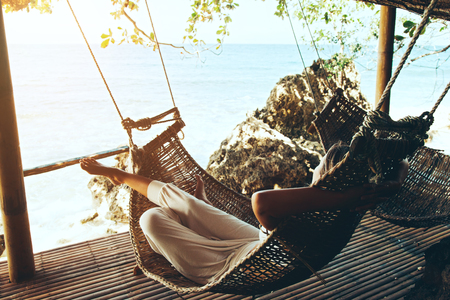 Photo pour Woman relaxing in the hammock on tropical beach, hot sunny day - image libre de droit